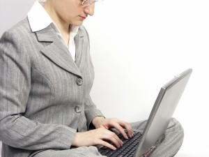 Woman with glasses sitting on a floor with laptop